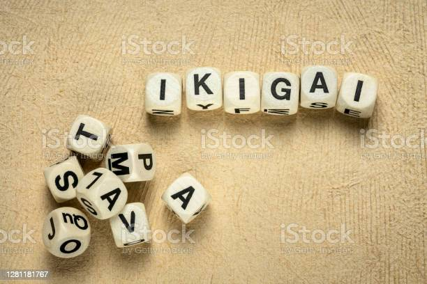 ikigai word abstract in wooden letter cubes against handmade bark paper, Japanese lifestyle concept  - a reason for being as a balance between love, skills, needs and money